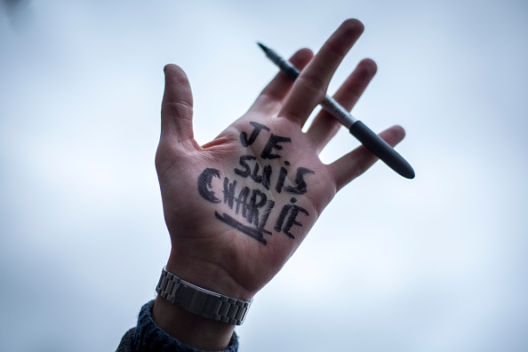 A man holds a pen aloft as people gather in Trafalgar Square to show their respect to victims of the terrorist attacks in Paris on January 11, 2015 in London, England.  London landmarks including Tower Bridge, Trafalgar Square and the National Gallery are to be lit in the blue, white and red colours of the French national flag later today in tribute to the 17 people killed in the Paris terror attacks. (Rob Stothard/Getty Images)