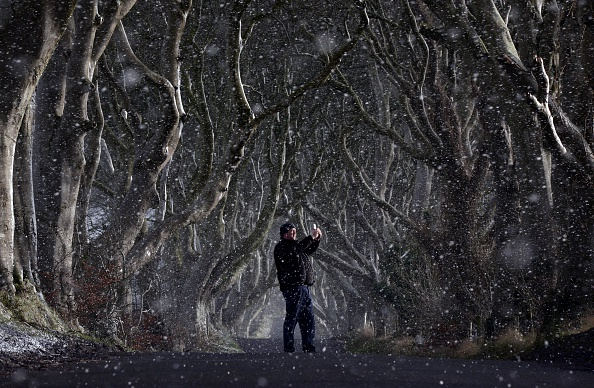Snow and freezing temperatures that hit Northern Ireland proivided this image of a man taking a picture with his mobile phone through heavy snow at the Dark Hedges. The Dark Hedges, named for it's unusual tree formation has become a recent tourist attraction after the setting was filmed as part of the hit HBO television series Game of Thrones which is filmed extensively in the province.  (Charles McQuillan/Getty Images)