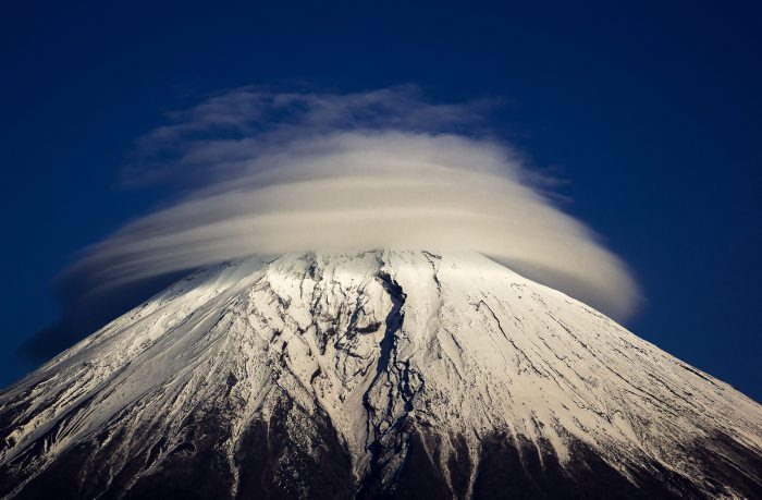 "This bizarre cloud formation has formed rings round the top of a mountain. The lenticular cloud sits atop the towering Mount Fuji, in Japan, during an otherwise blue skied day. The lens-shaped clouds are formed at high altitudes, when a moist air flow encounters obstructions - such as mountains or buildings - which disrupt the air flow and create standing waves in the atmosphere. These waves form on the downwind side and as the moisture in the air condenses, it forms these odd-shaped clouds. Photographer Akihiro Shibata spotted the clouds circling the top of Mount Fuji, which is the highest mountain in Japan at 3,776m, while at Yamanashi Prefecture Lake Tanuki, in Fujinomiya, Japan. The 41-year-old, from Matsumoto, Nagano Prefecture, in Japan, said: ""It was a beautiful cloud formation. ""I couldn't resist taking some photos even though I was actually there to take photographs of something else"". (Akihiro Shibata/Solent News/REX )"