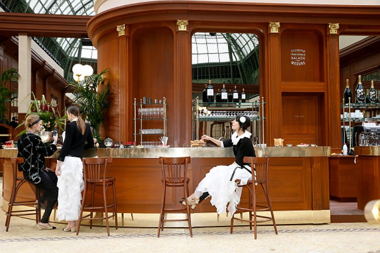 Illustration view of models standing at the Bar during the Chanel show. (Getty Images)