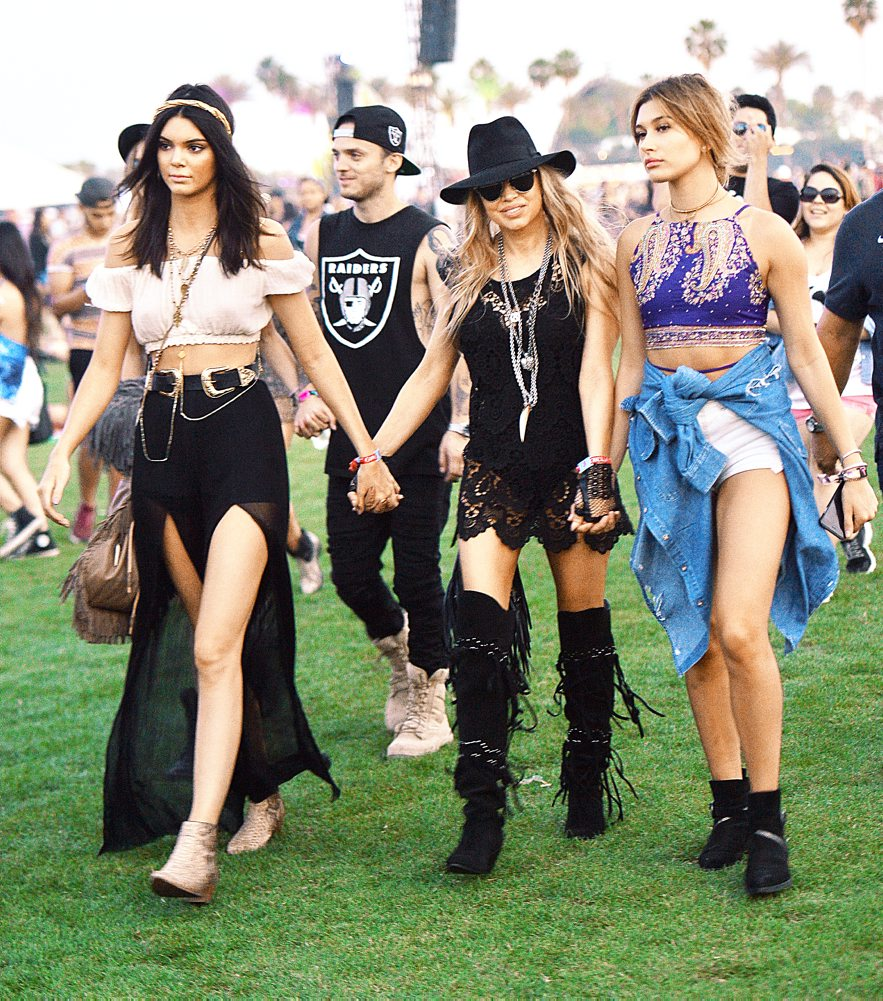 Kendall Jenner, Fergie, and Hailey Baldwin hold hands and dance while walking around Coachella in Indio, CA.